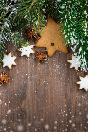 wooden background with fir branches, cookies and snow bokeh, top view, vertical