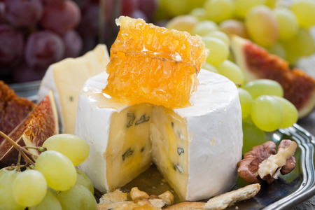 camembert with honey and fruit, snack on a plate, close-up, horizontal photo