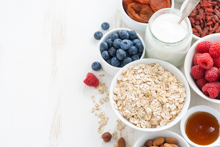 morning breakfast: cereal and various delicious ingredients for breakfast and white wooden background, top view