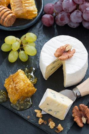 delicious Camembert with fresh honey and nuts, top view, vertical photo