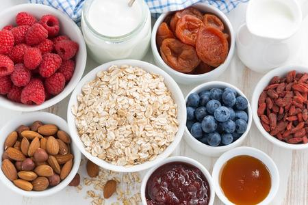 comiendo cereal: copos de avena y varios deliciosos ingredientes para el desayuno, vista superior, horizontal Foto de archivo