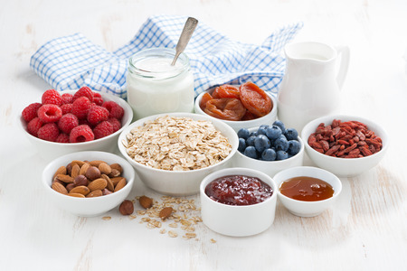 oat flakes and various ingredients for breakfast on white wooden table, horizontal