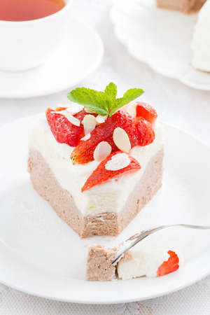 piece of delicious cake with whipped cream and strawberries, close-up photo