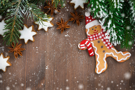 wooden background with fir branches, cookies and gingerbread man, snow bokeh, top view photo