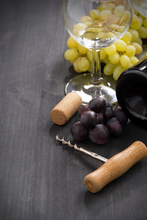 wine list: bottle of red wine, grape and corkscrew on a wooden background, vertical, close-up