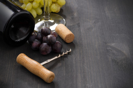 bottle of red wine, grape and corkscrew on a wooden background, horizontal