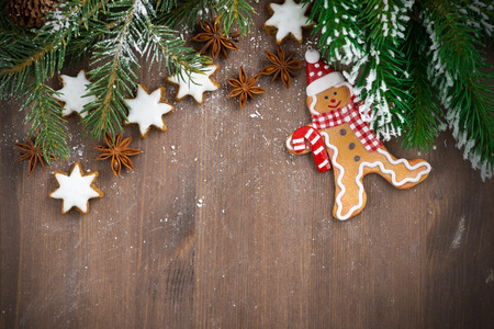 gingerbread man: wooden background with fir branches, cookies and gingerbread man, top view, close-up