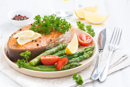 baked salmon with asparagus, parsley and lemon on plate photo