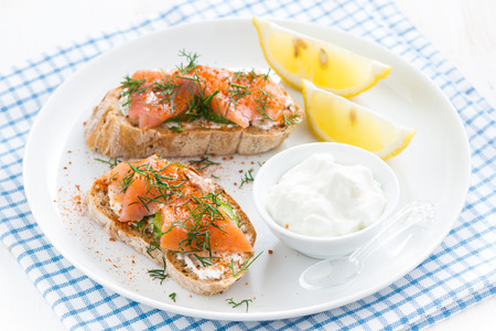 bread with salted salmon and cream cheese on a plate, top view photo