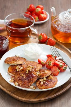 Breakfast. Pancakes with fresh strawberries and cream, jam and black tea, vertical photo