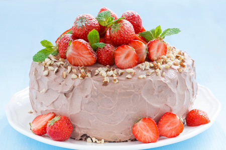 chocolate cake garnished with fresh strawberries on a blue background, close-up, horizontal photo