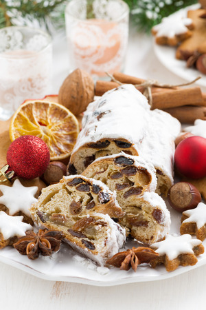 Christmas Stollen with dried fruit, cookies and spices on a plate, vertical photo