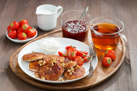 Delicious breakfast. Pancakes with fresh strawberries and cream, jam and black tea, close-up photo