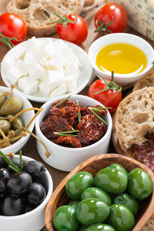antipasti: assorted Italian antipasti - olives, pickles and bread, top view, vertical