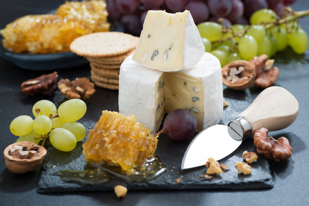 Camembert with fresh honey, grapes and nuts, horizontal photo