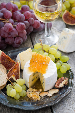 camembert with honey and fruit, snacks and wine on a plate, vertical, top view photo