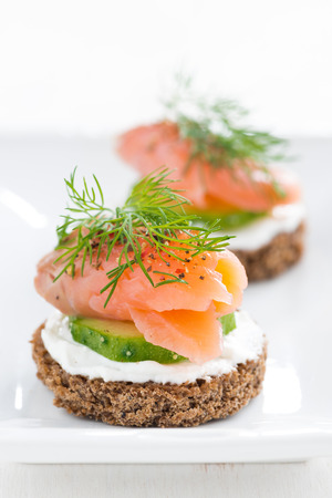 canape with cheese, cucumber and salmon, close-up, vertical Stock Photo