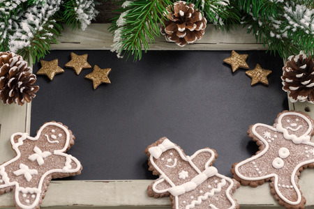Christmas concept. Black board for text and gingerbread man, close-up, selective focus, top view photo