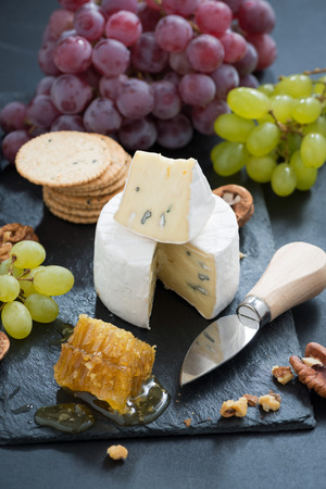 delicious Camembert with fresh honey, grapes and nuts on a dark background, vertical, top view photo