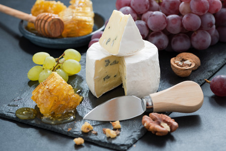 delicious Camembert with fresh honey, grapes and nuts, horizontal photo