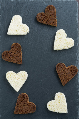 dark background with toasted rye and white bread in heart shape, top view, vertical photo