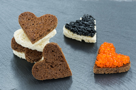 festive appetizer - toast with red and black caviar in the form of heart, horizontal photo