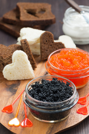 festive appetizer - toasts, red and black caviar, vertical, top view photo