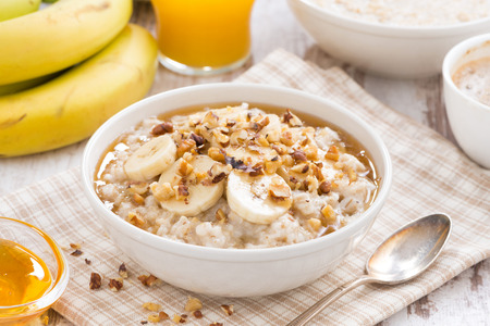 oatmeal with banana, honey and walnuts for breakfast, close-up