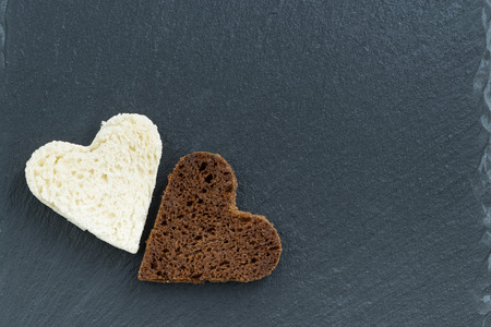 toasted rye and white bread in the form of heart on a dark background, top view, horizontal photo