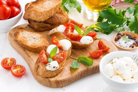 bruschetta with mozzarella, basil and cherry tomatoes, close-up photo
