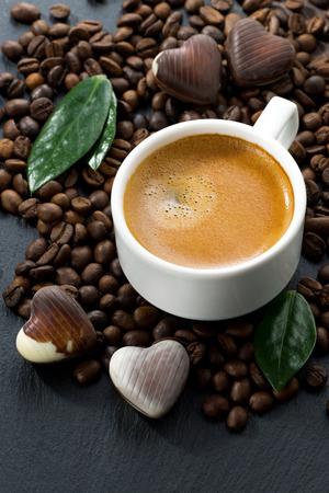 cafe bombon: taza de café en granos de café de fondo y dulces de chocolate en forma de corazón, vista vertical, de arriba