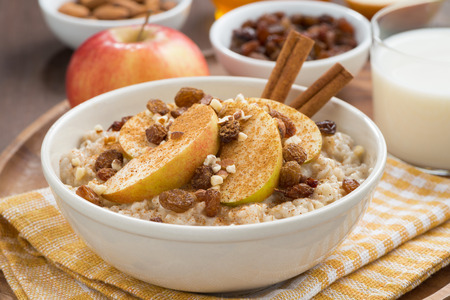 oatmeal with apples, raisins, cinnamon and ingredients, close-up, horizontal