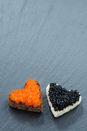 toast with red and black caviar in the form of heart on a dark background, top view, vertical, close-up photo