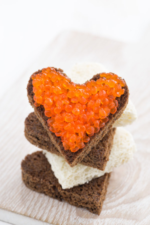 toast with red caviar in heart shape, close-up, vertical, top view