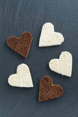 toasted rye and white bread in the form of heart on  black background, top view, vertical photo