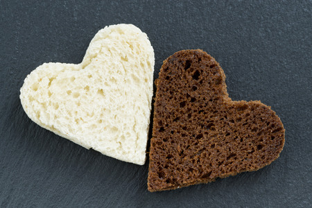 toasted rye and white bread in the form of heart on a dark background, close-up, top view photo