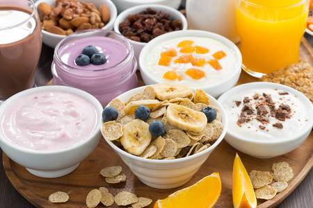 buffet: breakfast buffet with cereals, yoghurt and fruit on wooden tray, close-up, horizontal