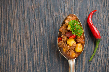 chili sauce: Mexican dish chili con carne in a spoon on a wooden background, concept photo, top view