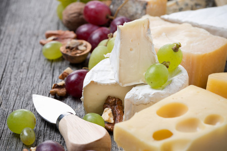dairy products: cheeses, grapes and walnuts on a wooden background, close-up