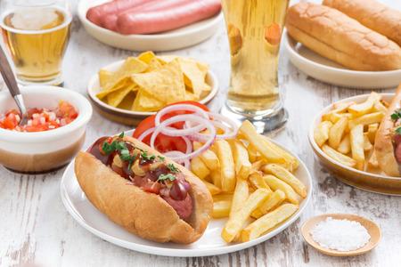 perro ba�era: hot dogs con papas fritas, cerveza y aperitivos Foto de archivo