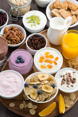 buffet: rich breakfast buffet with cereals, yoghurt and fruit on wooden tray, vertical, top view, close-up