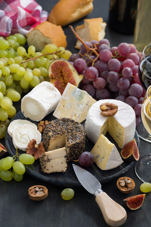 white cheese: soft delicacy cheeses and snacks for wine on a dark background, vertical, top view