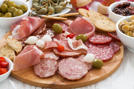 Assorted deli meat snacks, sausages and pickles on board, close-up