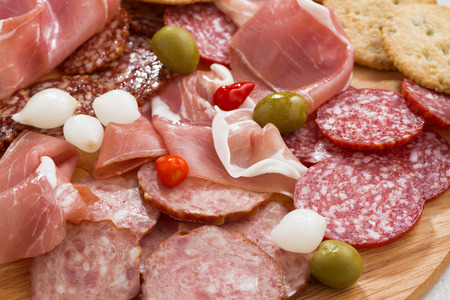 antipasto platter: Assorted deli meat snacks, sausages and pickles on board, close-up, horizontal