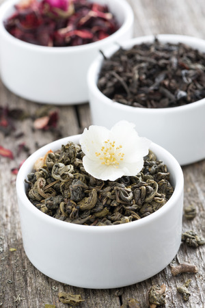 teas: Assorted dry herbal teas in white bowls, close-up