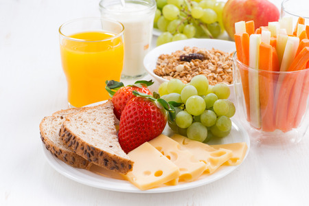 ni�os desayuno: desayuno saludable y nutritiva con frutas frescas y verduras en la mesa blanca, primer plano, horizontal Foto de archivo