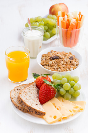 healthy and nutritious breakfast with fresh fruits and vegetables on white table, vertical