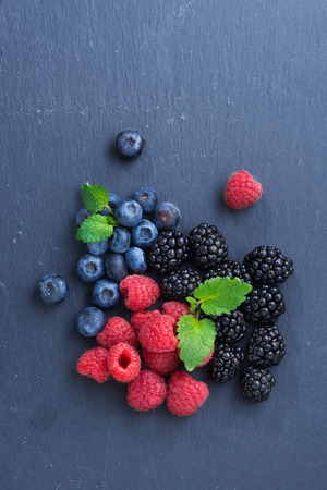Assorted fresh berries on a black background, top view, vertical, close-up Foto de archivo