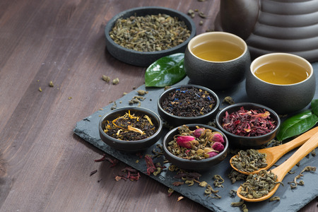 tea hot drink: assortment of fragrant dried teas and green tea on dark wooden table, horizontal