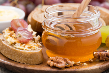 flavored honey, bread with butter and grapes, close-up, horizontal photo